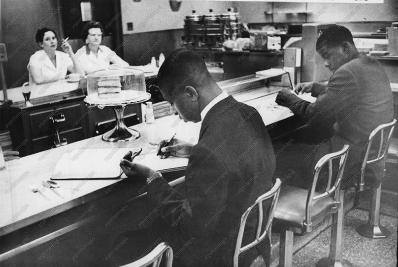 The Negro movement against segregated lunch counters in dime stores has spread throughout North Carolina. This picture shows two Negro students from St.Augustine College in Raleigh as they are ignored by waitresses who have taken seats behind counter at left.