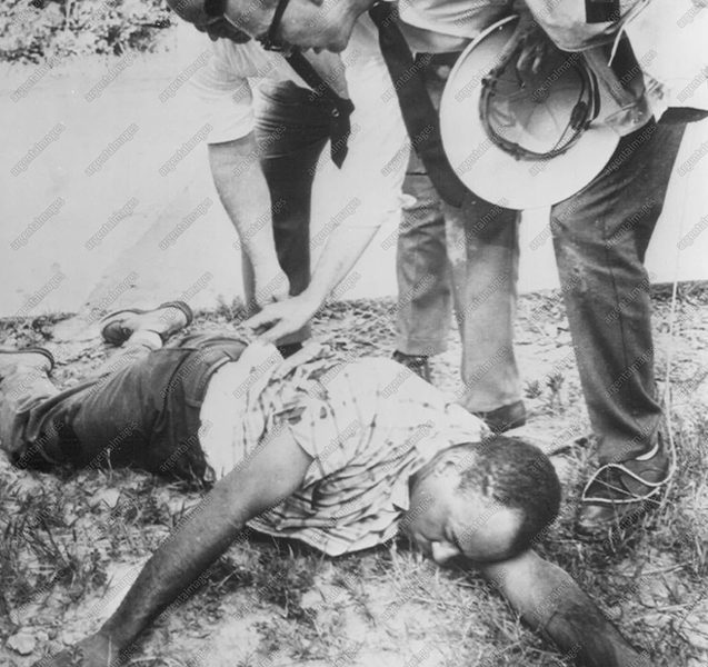 Meredith Lies Wounded--James Meredith lies on the side of Highway 51 in his blood-stained shirt after he was shot today during his march to Jackson, Miss. Unidentified officers are Havering over his body.