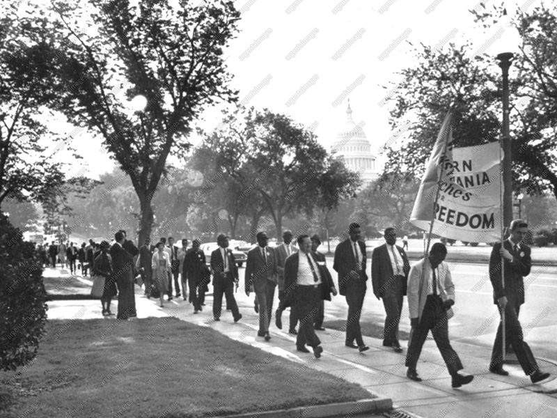 Pennsylvania Marchers--Western Pennsylvania civil rights demonstrators today follow sign-carrying leaders on their way to the Washington Monument headquarters of the March on Washington. In background is the Capitol. 1963