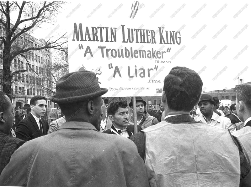 Josef-Miet, Polish freedom fighter, carrying an anti-King banner is surrounded for his own safety by Parade Marshalls. Dr. Martin Luther King will be leading a march from Roxbury section of Boston to the common 4/23.
