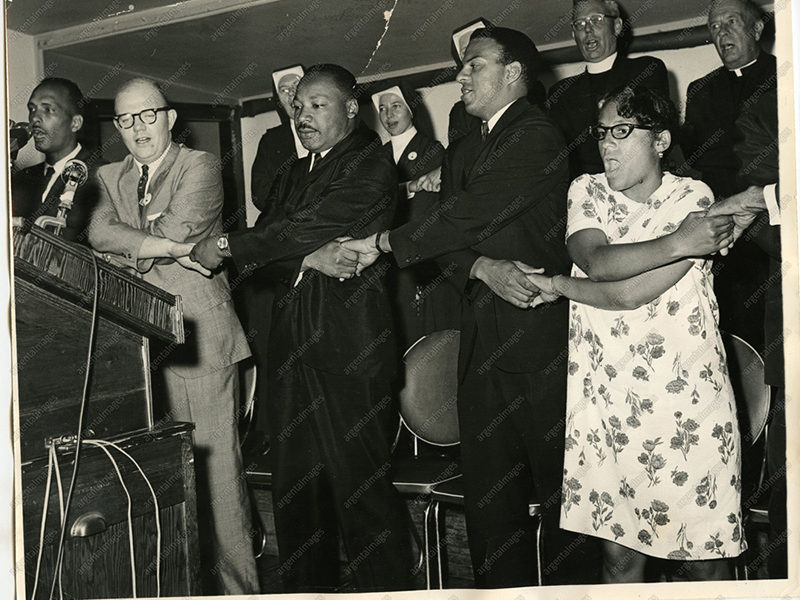 "1965 - Martin Luther King, Jr. Singing ""King leads the singing of We Shall Overcome after eulogizing a slain civil rights crusader, the Reverend James Reeb, Brown Chapel, Selma, Alabama. 1965 """
