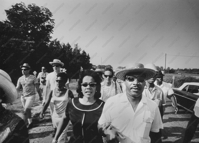 1966 - Martin Luther King Jr. and his wife Coretta march together along a rural Mississippi road with the March Against Fear.